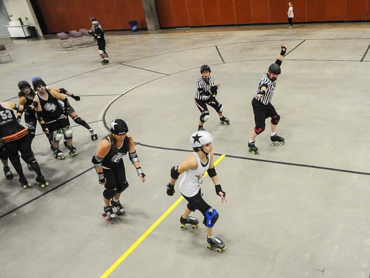 The jam ref on the right lets fans know who's got lead jammer by holding up one arm with fingers in an L-shape and pointing at the jammer with the other. The ref whose jammer doesn't have lead, (left,) will cross and uncross her arms repeatedly.