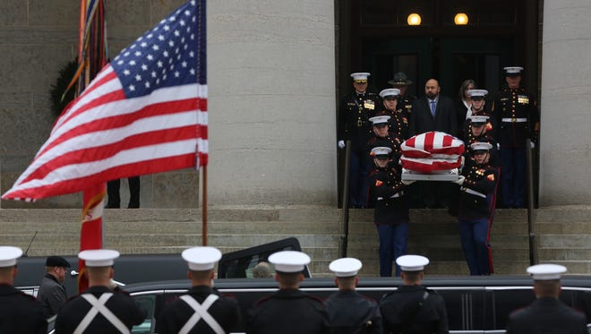 U.S. Marines carry former U.S. Sen. John Glenn's body out of the Ohio Statehouse and into a waiting hearse.