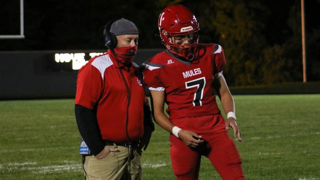 Bedford assistant football coach Jay Lake (left) talks with Brendan Hammer during a game earlier this season.
