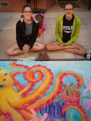 Reagan Mulvey and Rebecca Rieckmann sit by their Chalk Walk art in September 2014.