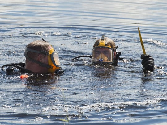Martin County Sheriff's Office dive team member Angelo Minella (right) brings up a blade June 1, 2016 at the Hungryland Wildlife and Environmental Area in Hobe Sound. Minella and fellow diver Justin Lundstedt (left) were searching the canal for evidence in the Tricia Todd murder case.