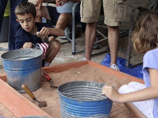 Alex Stephens and his sister Sophia dig through a sand box for hidden treasures at the 2016 Archeology Fair.