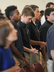 Braxton Madara, center, a junior, prays during the student Mass at St. Thomas More Academy in Magnolia.