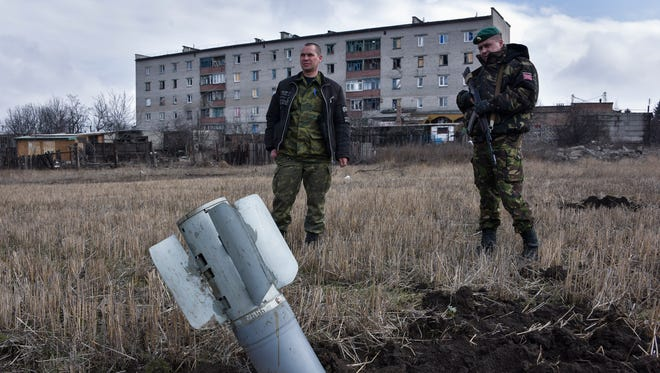 "Pro-Russian rebels look at an unexploded ""Uragan"" rocket in Debaltseve, eastern Ukraine on March 14."