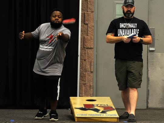 A.J. Sims (left), from Caldwell, tosses a beanbag while