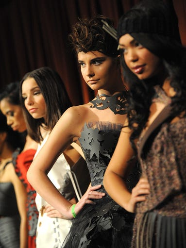 Models pose for photos during the fashion showcase,