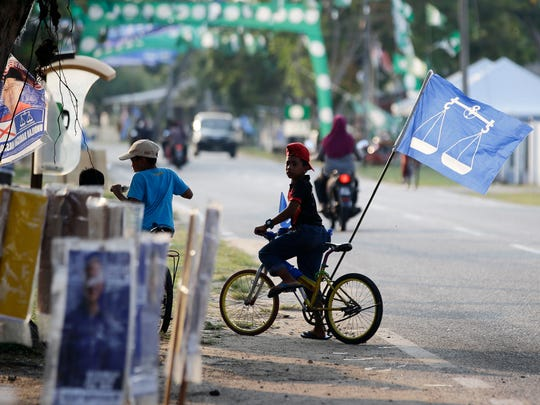 A boy rides on his bicycle with the flag of Malaysia's ruling National Front coalition at the hometown of Prime Minister Najib Razak in Pekan, Malaysia a day before the national elections on May 8, 2018. Malaysian scandal-plagued Prime Minister Najib Razak is seeking a third term in office during the May 9 general election, but faces an unprecedented challenge from a rejuvenated opposition led by his former mentor and strongman Mahathir Mohamad.