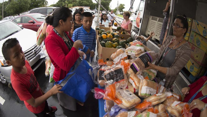 People pick out items from a mobile food pantry put on through the Harry Chapin Food Bank.