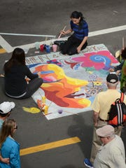 Morgan Bailey works on a panel featuring sunset colors. People strolled all over Fifth Avenue as Chalk Art 2017 turned it into a pedestrian mall on Saturday in the fundraising event.