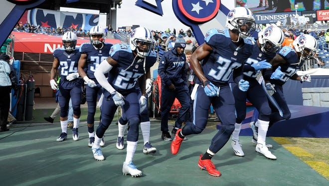 Titans cornerbacks Jason McCourty (30) and Brice McCain (23) and their teammates run onto the field before the game against the Broncos at Nissan Stadium Sunday, Dec. 11, 2016, in Nashville, Tenn.
