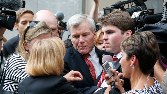 Media mobs former Virginia governor Bob McDonnell, center, as he gets into a car Sept. 4, 2014, with his son, Bobby, right,  after he and his wife, former first lady Maureen McDonnell, were convicted on multiple counts of corruption in federal court in Richmond, Va.
