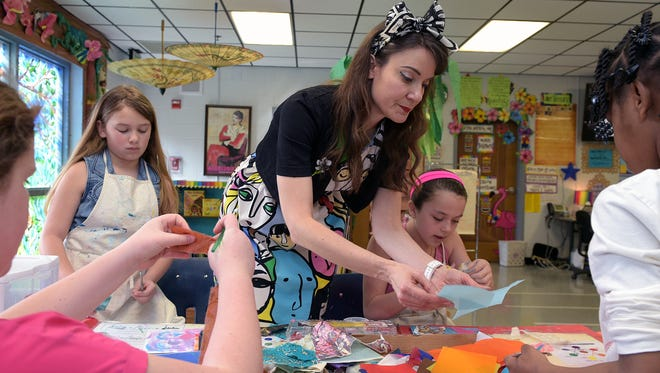 Johnson Elementary art teacher Cassie Stephens wears funky outfits every day to inspire her students. Stephens helps fourth-graders Reese Thompson, left, and Sophia Lilly with an art project in class on March 9, 2016.