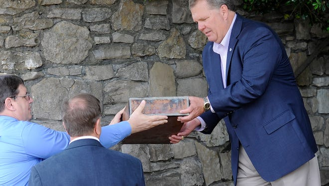 Randy Davis, of the Tennessee Baptist Convention Center, is handed a time capsule that was placed behind a stone in 1969 when the building was first constructed in Brentwood. The group is moving soon to smaller, leased offices in Nashville. The ceremony was held Monday, May 19, 2014, in Brentwood, Tenn.