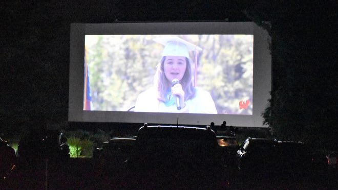Wells High School senior Elliana Poulin sings the National Anthem during a pre-taped graduation ceremony for the Class of 2020. The recording was screened Thursday, June 11, at the Saco Drive-in, so the graduates and their guests could maintain a safe distance from one another amid the COVID-19 pandemic.