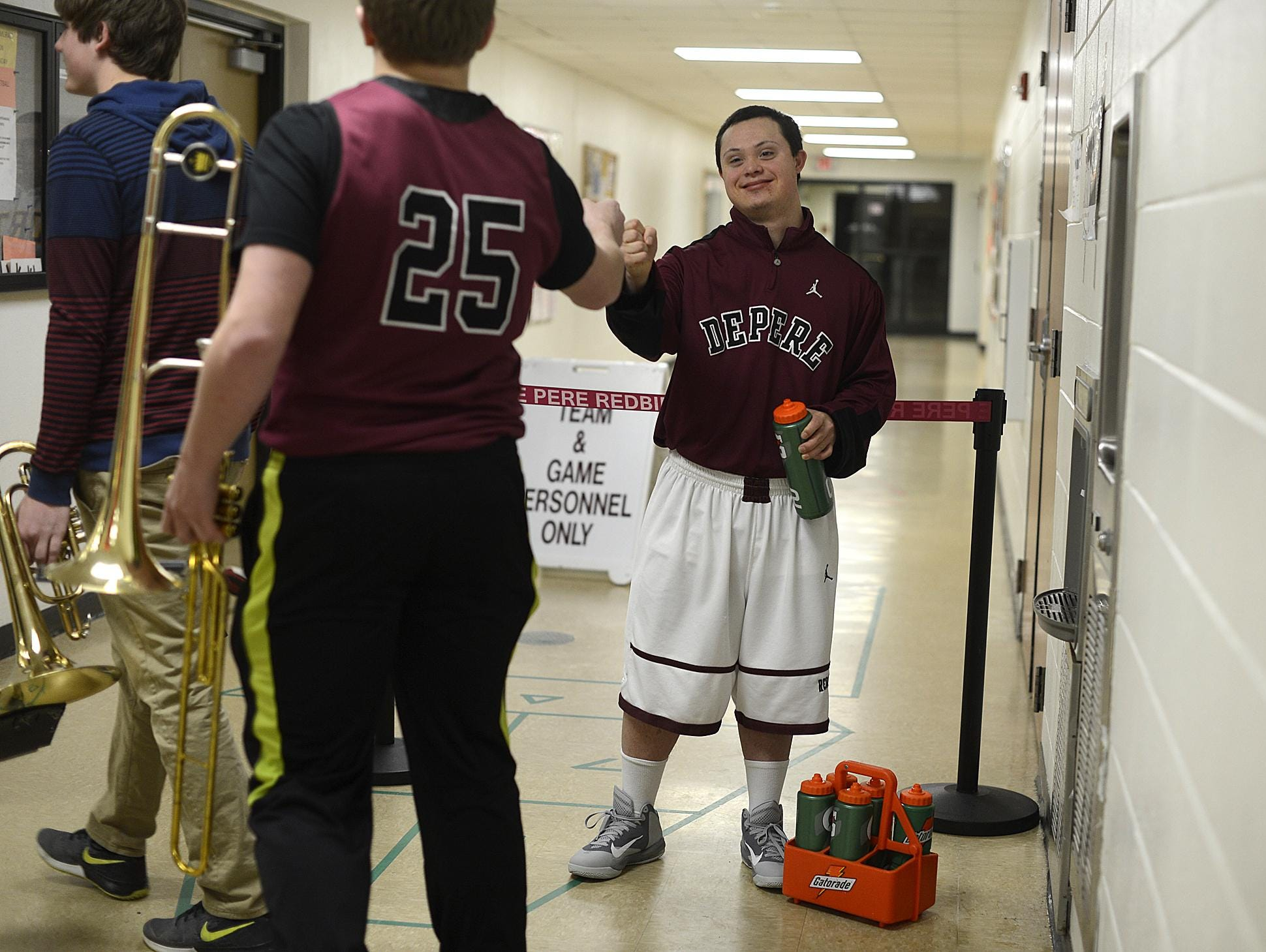 At right, Nate Wagner gets ready for his first game as a player against Sheboygan North.
