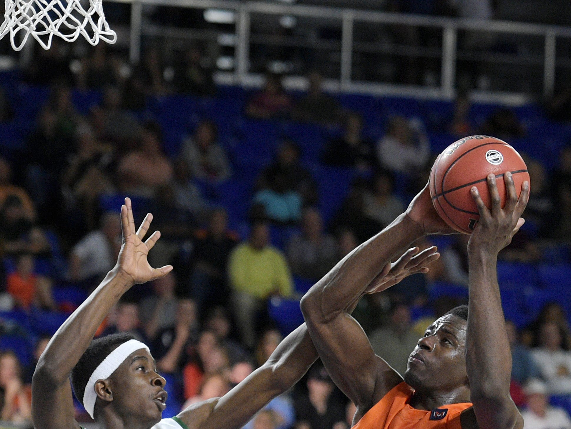 Nashville Christian's Daniel Bituli (35) scores against Booker T. Washington's Tyrone Sumlin (15) during the Boys Class A State quarterfinal game at MTSU's Murphy Center on Wednesday.
