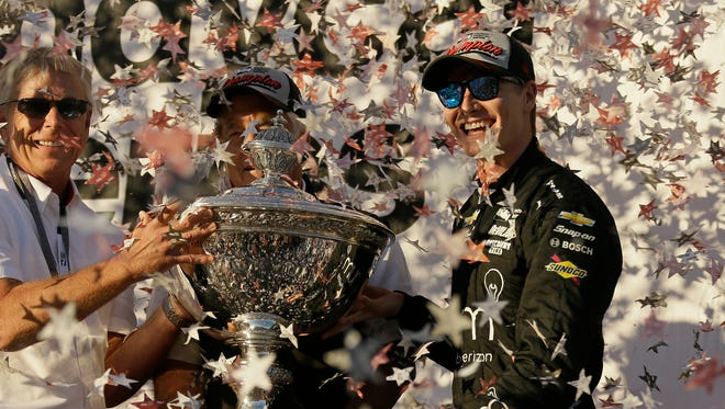 Josef Newgarden, right, stands and celebrates after being presented the Astor Cup for winning the IndyCar championship Sunday, Sept. 17, 2017, in Sonoma, Calif. Looking on at center is team owner Roger Penske.