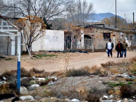A group of people walk on Jan. 4, 2016, in a Juarez, Mexico, neighborhood across the border from Sunland Park, N.M.