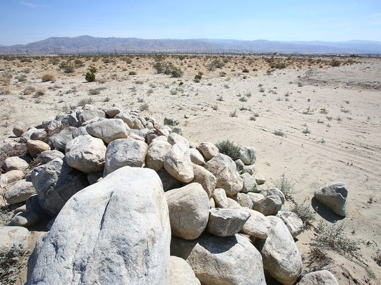Large boulders are stacked near the roadside from nearby grated land where a large-scale commerical marijuana cultivation zone has sprung up on LIttle Morongo Rd in Desert Hot Springs, June 8, 2016.