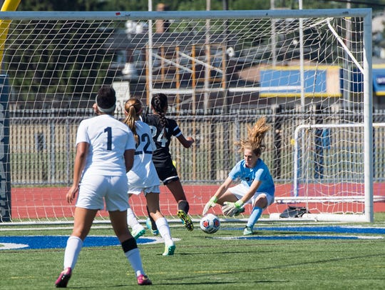 Chambersburg goalkeeper Caitlin Masaberg gets to the