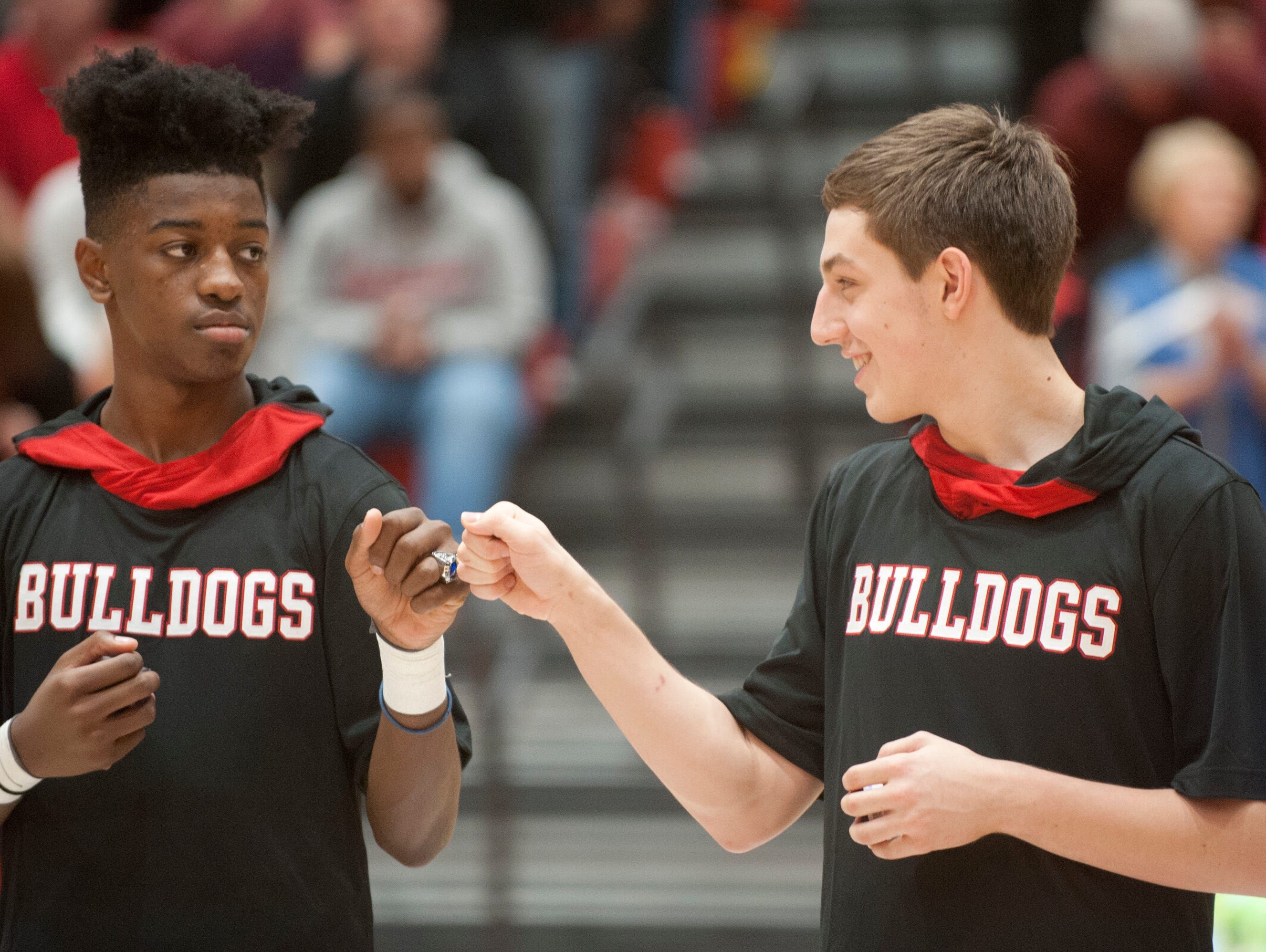 New Albany's Sean East knocks 2016 Indiana High School Boys Basketball Championship rings with teammate Isaac Hibbard after the entire team was honored prior to start of the game against Bloomington South. 26 November 2016