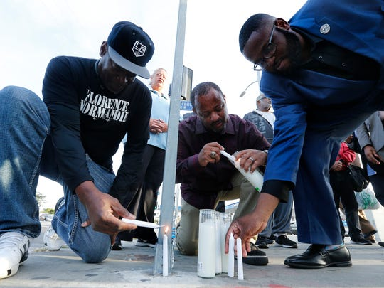 South Los Ageles resident Timothy Goldman (from left); Najee Ali, political director of the National Action Network; and K.W. Tulloss, Western Regional director of the National Action Network, light candles during a prayer vigil and moment of silence Monday, April 24, at the intersection of Florence and Normandie in South Los Angeles, to remember all those who lost their lives 25 years ago in the worst race riot in U.S. history.