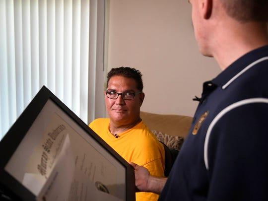 Director of Communications at Murray State University Shawn Tourney presents Henderson resident Allen Stone with his Bachelor of Integrated Studies diploma Friday. Stone is paralyzed and has been diagnosed with Guillian Barre Syndrome, June 16, 2017.