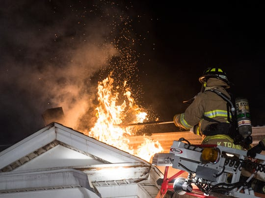 Firefighters work on containing a house fire at 340