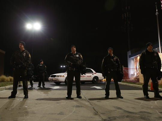 FERGUSON, MO - NOVEMBER 24:  St. Louis County police officers stand guard in front of the Ferguson police department on November 24, 2014 in Ferguson, Missouri. A St. Louis County grand jury has reached a decision on whether or not to charge Ferguson police Officer Darren Wilson in the shooting of Michael Brown that sparked riots in Ferguson, Missouri in August.  (Photo by Justin Sullivan/Getty Images)