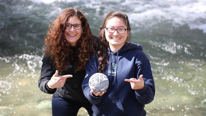 Rachael Miller, left, co-founder and executive director of the Rozalia Project, and Brooke Winslow, research coordinator for Rozalia Project and co-inventor of the microfiber catcher, show off a prototype of the device, which catches microfibers in the clothes washing machines before they drain out with the water.