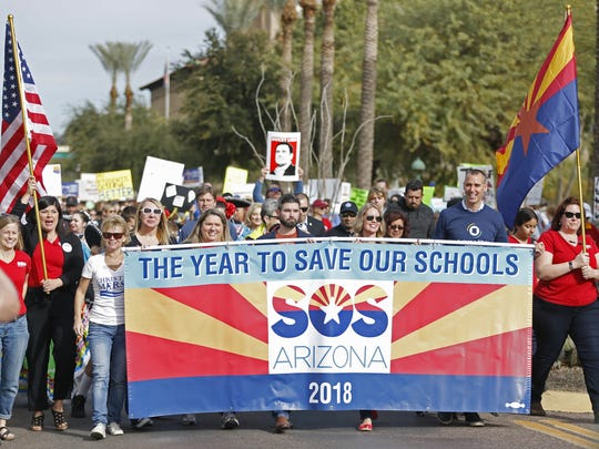 People begin marching during a Save Our Schools rally outside the State Capitol on Jan. 6, 2018, in Phoenix, Ariz.