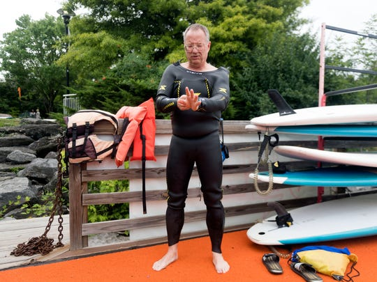 "Brian Bischoff wears a wet suit for an open water swim at Fort Loudoun Lake on Thursday. Despite an active lifestyle, Bischoff had a heart attack in January. He was back to training for triathlons three months later. """"I pretty much wrote off my year when the heart attack happened,"" Bischoff said."