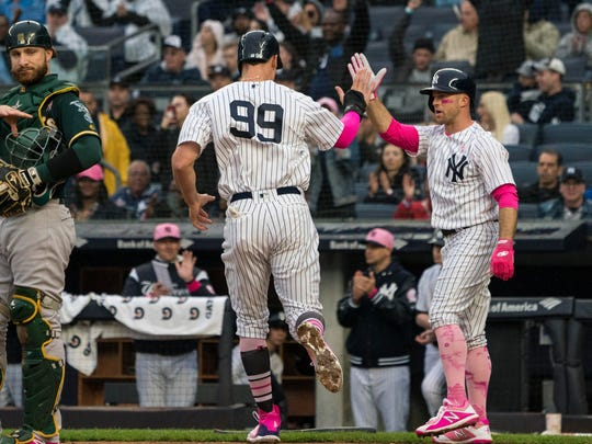 New York Yankees right fielder Aaron Judge (99) scores a run along with left fielder Brett Gardner (11) on right fielder Giancarlo Stanton (27) (not pictured) RBI single during the first inning.