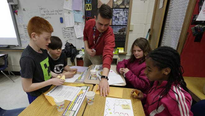 Ben Rush, a Farm to School AmeriCorps member with the Winnebago County Health Department, works recently with students, from left, Jonathan Morrisson, Joaquin Aguilar, McKenzi Schrank-Hayden and Marjana Wilson at Webster Stanley Elementary School in Oshkosh.