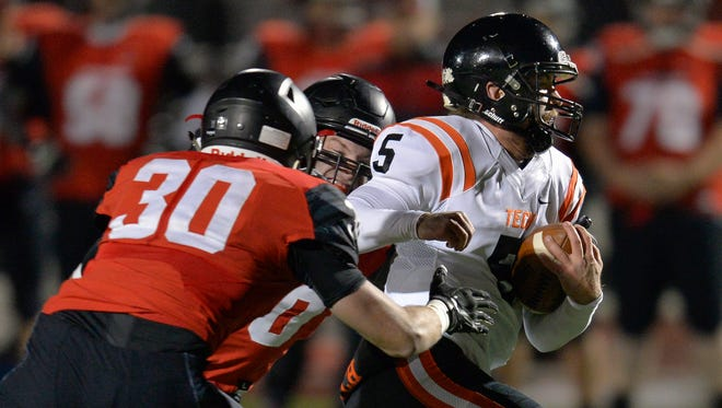 St. Cloud Tech quarterback Chris Backes (5) tries to drive the ball forward under pressure from Alexandria's Quintin Kluver-Longfellow (30) and another defender in the first half Wednesday at Alexandria Area High School.