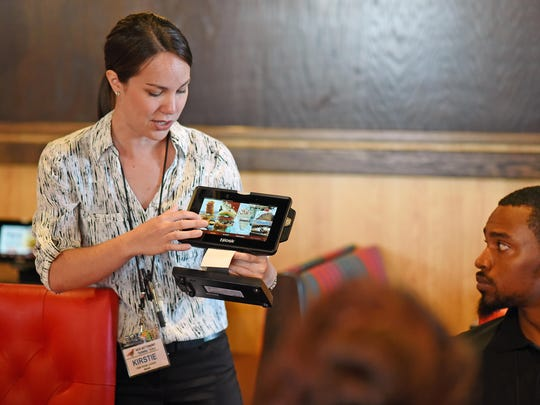 Kirstie Roy, of Maine, a new restaurant trainer talk to trainees about a Robin device that customers can order food, drinks and games. The new Red Robin will open this Monday on Delsea Drive in Vineland. August 5, 2015. Staff photo/Craig Matthews