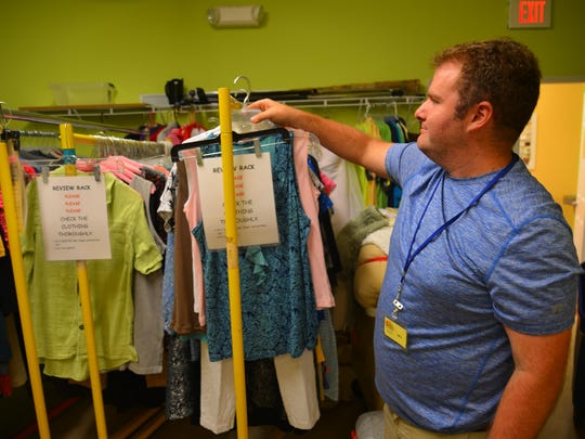 Greg Ashner hangs up clothes that have been donated to the thrift shop. He serves on the Promise in Brevard advisory council, representing the wants and needs of future Promise residents.
