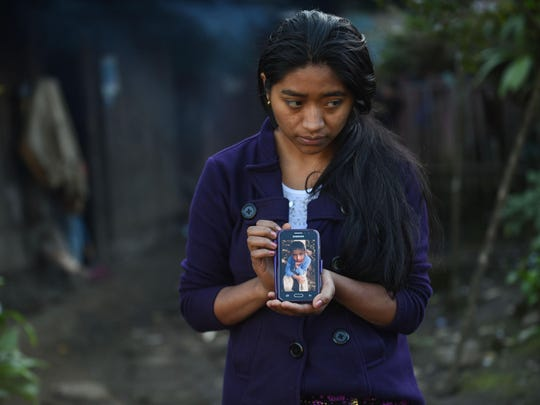 Catarina Gomez Lucas, sister of eight-year-old migrant Felipe Gomez, who died in a medical center in Alamogordo, New Mexico, United States, on December 24, while in custody of US Customs and Border Protection officers, shows a picture of her brother on a mobile phone outside her house in Yalambojoch village, Nenton municipality, Huehuetenango department, 400 km northwest Guatemala City on December 28, 2018.