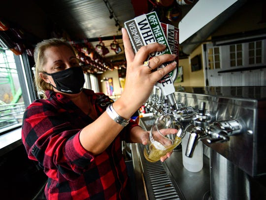 Nancy Wheeler Sage, lead bartender at the Whetstone Station in Brattleboro, Vt., pours a beer Friday. After Vermont saw its highest daily number of coronavirus cases this week, Gov. Phil Scott has announced new restrictions on social gatherings and bars.