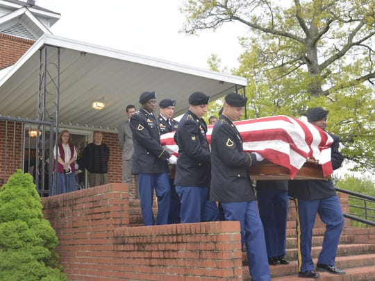 A military honor guard from Fort Bragg bear the casket of Sgt. Arnold Pitman down the steps of Laurel Hill Baptist Church near Dysartville. Pitman was buried Sunday with full military honors in his family cemetery 65 years after he was listed as missing in action in Korea.