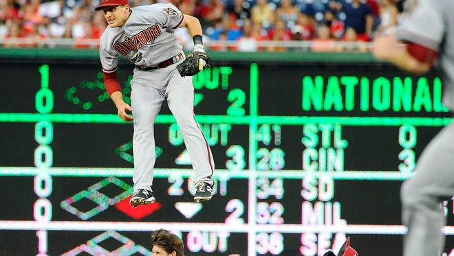 Aug. 4, 2015; Washington, D.C.; Washington Nationals baserunner Bryce Harper  slides into second base under  leaping Arizona Diamondbacks shortstop Nick Ahmed (13) for a double during the first inning at Nationals Park.