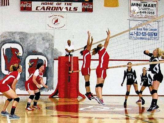 Corona High School's Payton Dunsworth and Chelby Brown leap for the block, helping the team defeat Animas 3-0 Sept. 4.