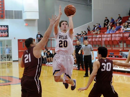 Wylie's Sam King (20) goes up for a shot between Vernon's Marc Rodriguez (21) and Nolan Chavez (30) during the Bulldogs' 91-43 win in the Region I-4A bi-district playoff in Olney on Monday, Feb. 19, 2018.