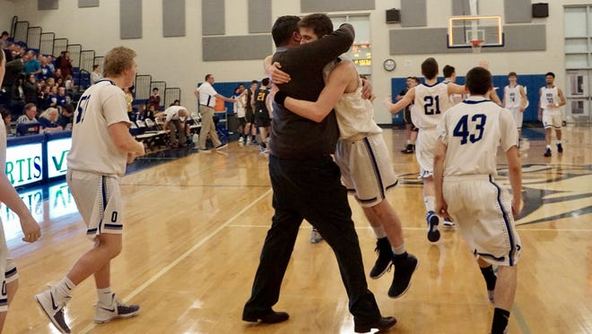 Olympic senior Tyler Yost gets a hug from coach Devin Huff after Thursday's victory against Fife in a the Class 2A West Central District Tournament.
