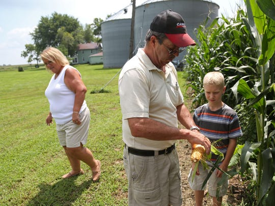 Kelly and Gina Bennett check corn with their grandson, Owen Morris on Wednesday afternoon, Aug. 3, 2016, at the Bennett's farm in rural Keota. The farm has been in the family for six generations.