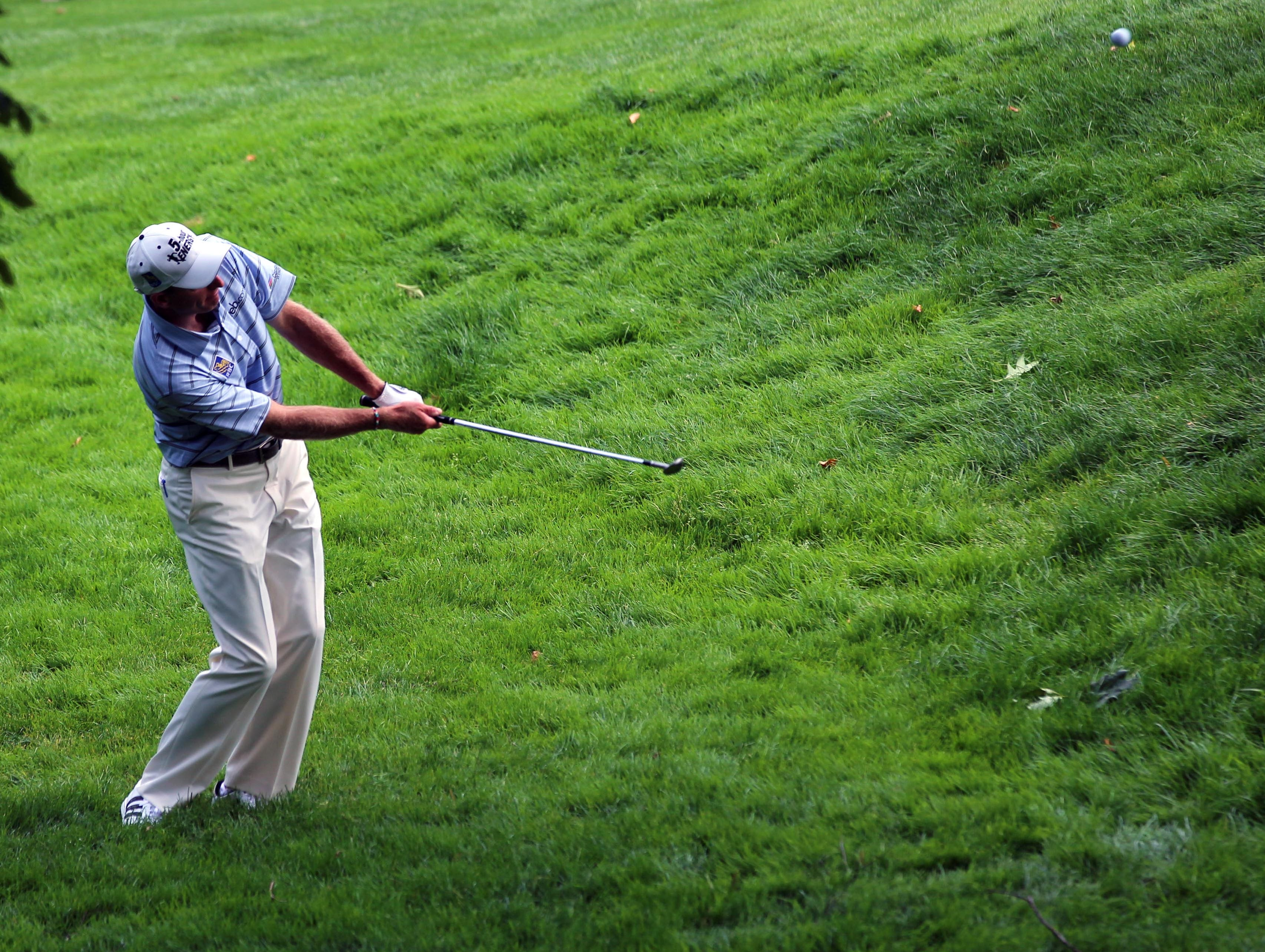 Jim Furyk plays a shot from the rough on the 9th hole. He shot a 65.