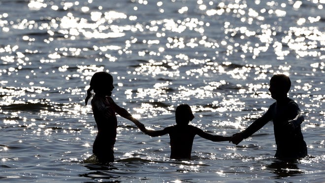 Kate Mitchell, 8, left, cools off along the shores of Lake Winnebago with her friends Lian Lewis, 8, and Ben Lewis, 13,  at High Cliff Park in Sherwood, WI.