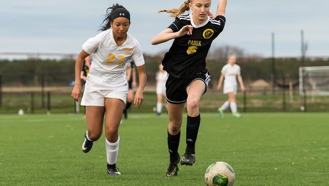 Riley Hickox of Padua (right) sprints past Caesar Rodney's Laynee Ford during the Pandas' 6-1 win on April 3.