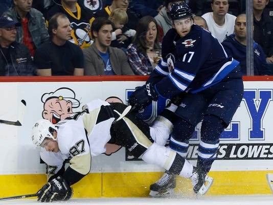 Winnipeg Jets' Adam Lowry (17) dumps Pittsburgh Penguins' Sidney Crosby (87) during the second period of an NHL hockey game Thursday, Nov. 6, 2014, in Winnipeg, Manitoba. (AP Photo/The Canadian Press, John Woods)