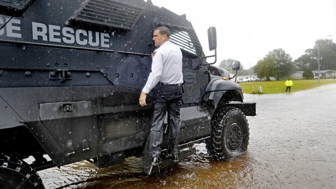 Maj. James Nolette with the Fayetteville police department hangs onto a high water vehicle while evacuating residents from a flooded neighborhood as Florence continues to dump heavy rain in Fayetteville, N.C., Sunday, Sept. 16, 2018. (AP Photo/David Goldman)